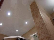 Белый глянцевый потолок в ванной комнате с потолочными светильниками
