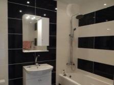 Стены маленькой ванной облицованные контрастной отделкой