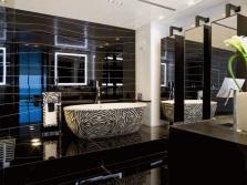 Стена в ванной из зеркальной плитки черного цвета