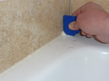 Заделка щелей между ванной и стеной при помощи герметика