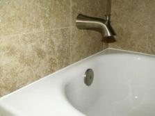 Заделка зазоров между ванной и стеной при помощи силиконового герметика