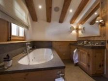 Деревянные балки, потолочные светильники и побеленные стены в ванной в стиле шале