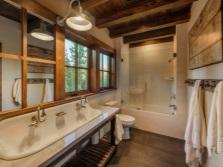 Деревянные потолки, одиночный металлический светильник, побеленные стены, каменные полы - это ванная в стиле шале