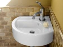 Маленький фарфоровый умывальник в небольшой ванной комнате