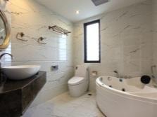 Угловая ванна с гидромассажем, столешница под раковину из черного мрамора и электронный унитаз в итерьер ванной комнаты, совмещенной с туалетом