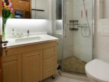 Вместительная тумба с раковиной  и маленькая душевая кабина в интерьере небольшой ванной комнаты, совмещенной с туалетом