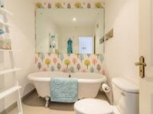 Интерьер ванной комнаты, совмещенной с туалетом в белом цвете с небольшими яркими акцентами на одной стене