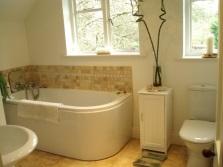 Интерьер небольшой ванной комнаты, совмещенной с туалетом с маленькой тумбой под ванные принадлежности