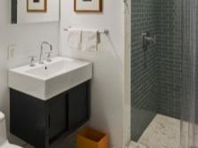 Выделение душевой зоны серым цветом в белой ванной комнате