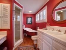 Красный интерьер ванной комнаты, совмещенной с туалетом с белой мебелью и сантехникой