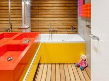 Желтая ванна, оранжевые раковины в интерьере ванной комнаты, совмещенной с туалетом