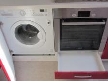 стиральная машина, встроенная в кухонный гарнитур красного цвета
