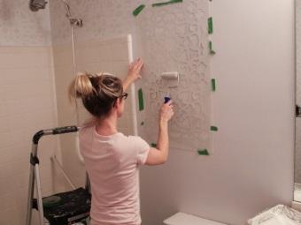 Нанесение краски на трафаретный рисунок в ванной при помощи валика