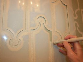 Нанесение краски на трафаретный рисунок в ванной при помощи кисти