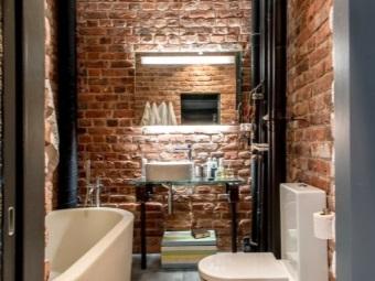 Кирпичные стены, белая сантехника и стеклянная мебель в ванной в стиле лофт