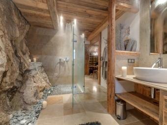 Каменные полы и стены, деревянная мебель в ванной в стиле шале