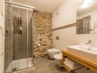 Белые и каменные стены в ванной в стиле шале