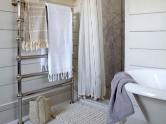 Нижний водяной полотенцесушитель с полотенцами в ванной - достоинства