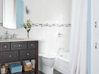 Вместительная напольная тумба черного цвета со встроенной раковиной в белом интерьере ванной комнаты, совмещенной с туалетом
