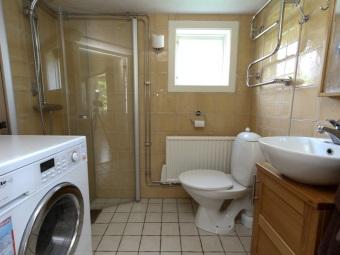 Интерьер ванной комнаты, совмещенной с туалетом вмещающий в себя душевую кабину, стиральную машину, тумбу под раковину и унитаз