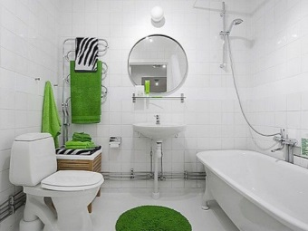 Интерьер белой ванной комнаты, совмещенной с туалетом с яркими акцентами в виде зеленых полотенец и коврика