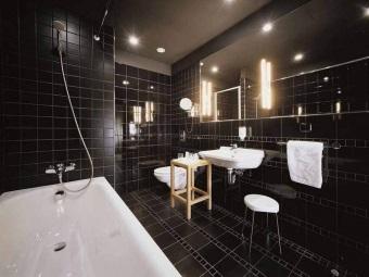 Совмещенная с туалетом черная ванная комната, с белой сантехникой