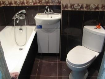 белый угловой унитаз в ванной с темными стенами