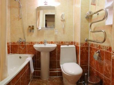 Маленькая ванная комната с белой сантехникой и полотенцами