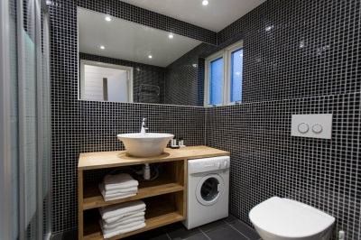 Стиральная машина в ванной комнате с раковиной на одной столешнице