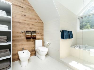 Ванная комната в скандинавском стиле - стены из настоящего дерева, белая ванна, белый потолок, полотенца с национальным скандинавскими узороми