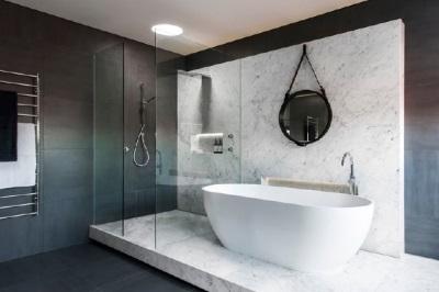 Овальная ванна и душевая кабина на подиуме из мрамора в хай-тек ванной