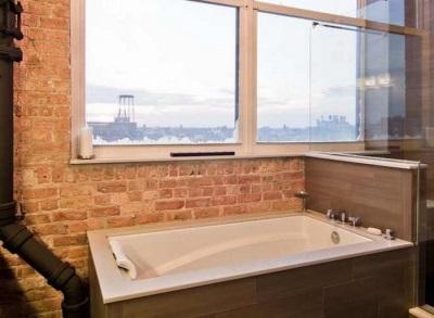 Ванная комната с кирпичными стенами, большими окнами и не скрытой коммуникацией в стиле лофт