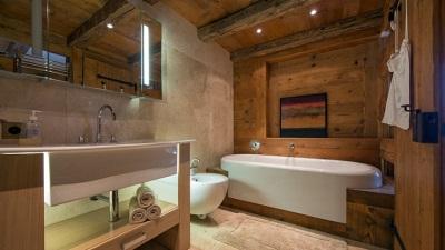 Точечный свет на деревянном потолке с балками в ванной в стиле шале