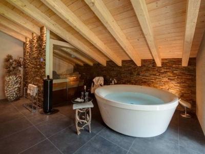 Ванная комната в стиле шале - деревянные потолки, большая ванна, каменные стены и полы