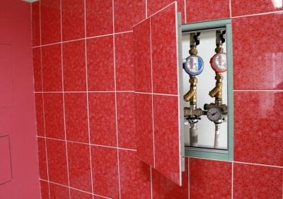 Ревизионный сантехнический люк невидимка отделанный красной керамической плиткой