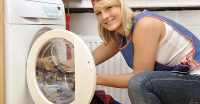Женщина вытаскивает белье из стиральной машины