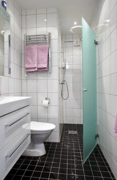 Слив в полу в душевой кабине в маленькой ванной